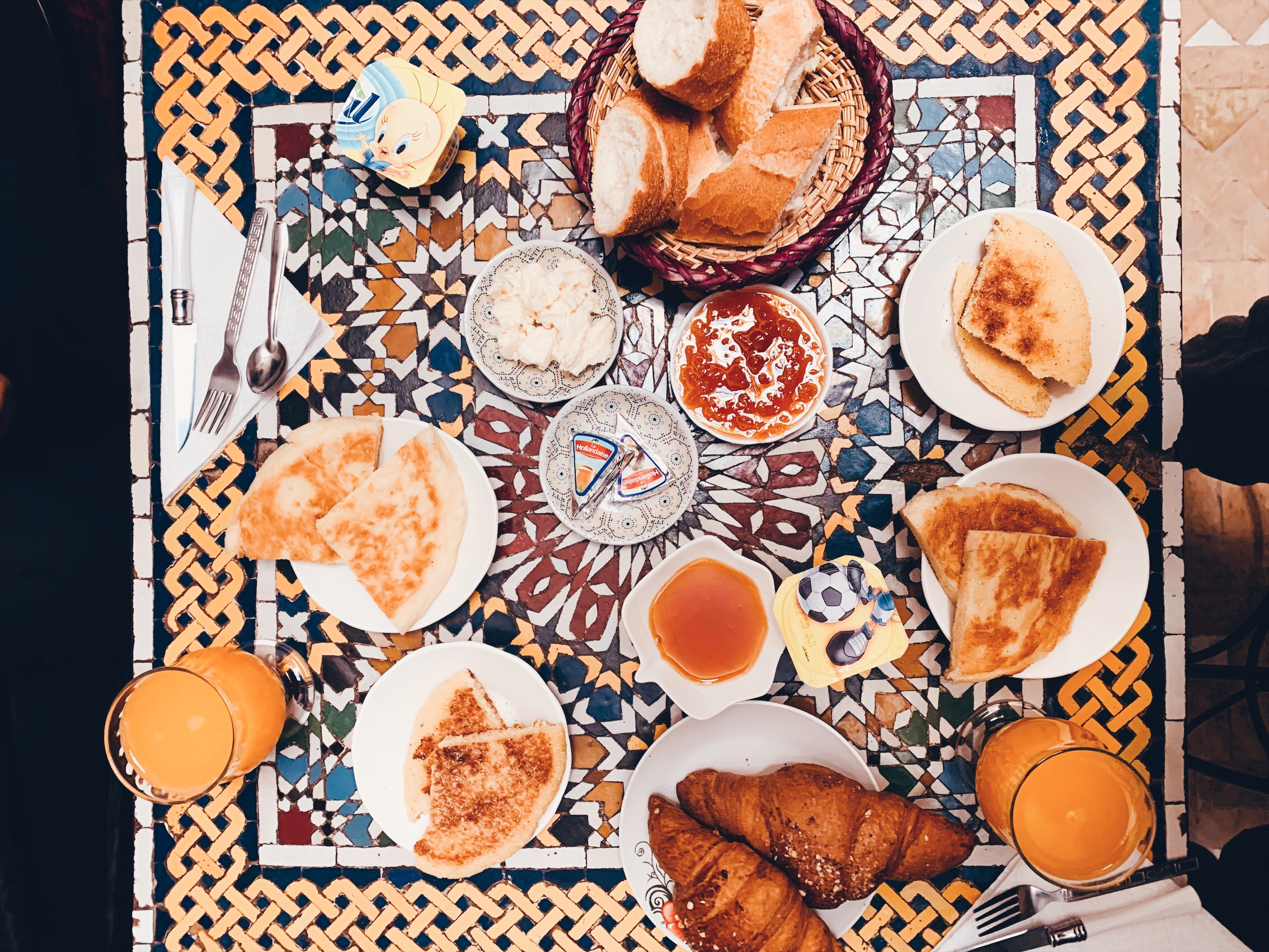 A huge breakfast is spread out on an intricate mosaic table.